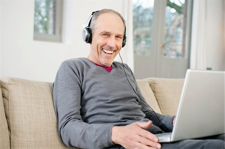 Man using a laptop and listening to music Stock Photo - Premium Royalty-Free, Code: 6108-05867457