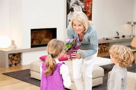 Woman giving a potted plant to her granddaughter Stock Photo - Premium Royalty-Free, Code: 6108-05867667