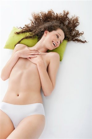 Woman covering her breasts and smiling Stock Photo - Premium Royalty-Free, Code: 6108-05867759