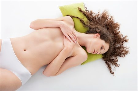 Woman covering her breasts and sleeping Stock Photo - Premium Royalty-Free, Code: 6108-05867777