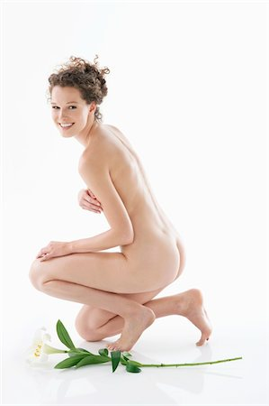 Naked woman kneeling beside a flower and smiling Stock Photo - Premium Royalty-Free, Code: 6108-05867791