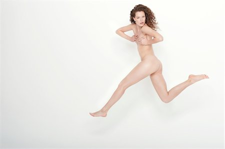 Naked woman covering her breasts and jumping Stock Photo - Premium Royalty-Free, Code: 6108-05867797
