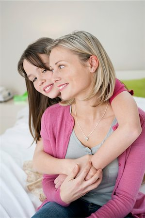 Girl hugging her mother from behind Stock Photo - Premium Royalty-Free, Code: 6108-05867716