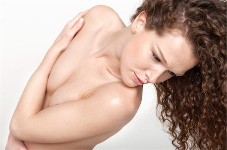 Woman covering her breasts Stock Photo - Premium Royalty-Free, Code: 6108-05867803
