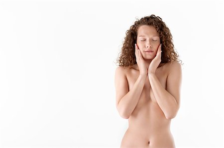 Close-up of a woman touching her cheeks Stock Photo - Premium Royalty-Free, Code: 6108-05867812