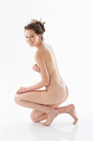 Naked woman covering her breasts and smiling Stock Photo - Premium Royalty-Free, Code: 6108-05867815