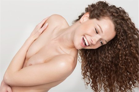 Woman covering her breasts and smiling Stock Photo - Premium Royalty-Free, Code: 6108-05867821