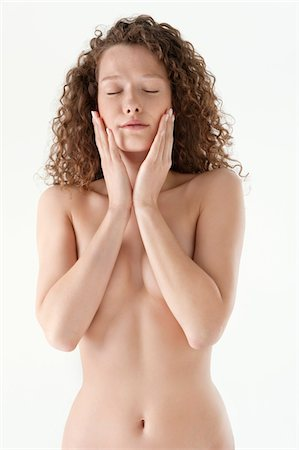 Close-up of a woman touching her cheeks Stock Photo - Premium Royalty-Free, Code: 6108-05867833