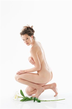 Naked woman kneeling beside a flower Stock Photo - Premium Royalty-Free, Code: 6108-05867835
