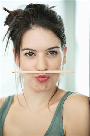 pucker - Woman balancing a pencil on lip Stock Photo - Premium Royalty-Free, Code: 6108-05868247