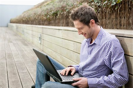 Man using a laptop on a boardwalk Stock Photo - Premium Royalty-Free, Code: 6108-05868540