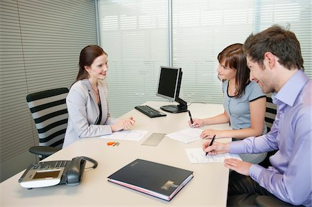 Couple signing agreement form in a real estate agent's office Stock Photo - Premium Royalty-Free, Code: 6108-05868645