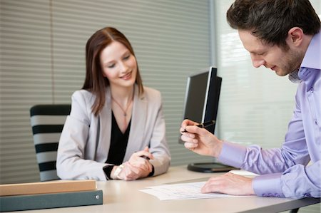 form - Man signing documents with a female real estate agent sitting in front of him Stock Photo - Premium Royalty-Free, Code: 6108-05868657