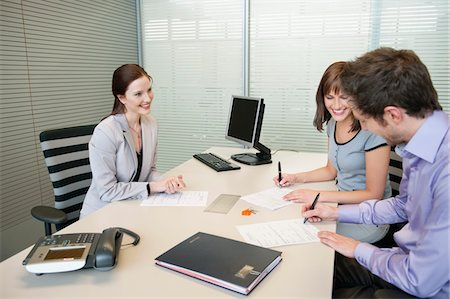 Couple signing agreement form in a real estate agent's office Stock Photo - Premium Royalty-Free, Code: 6108-05868662