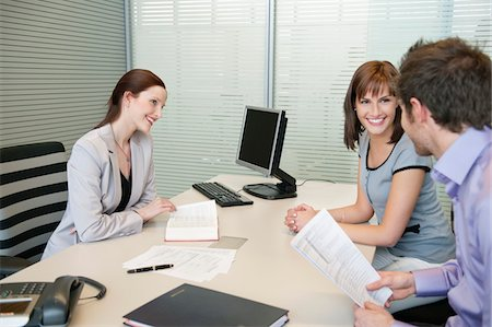 Female real estate agent and a couple discussing in an office Stock Photo - Premium Royalty-Free, Code: 6108-05868664