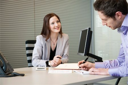 Man signing documents with a female real estate agent sitting in front of him Stock Photo - Premium Royalty-Free, Code: 6108-05868669