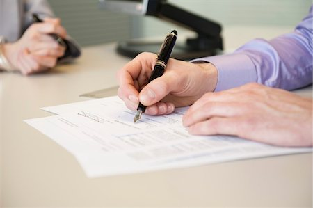 Man signing documents Stock Photo - Premium Royalty-Free, Code: 6108-05868619