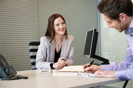 Man signing documents with a female real estate agent sitting in front of him Stock Photo - Premium Royalty-Free, Code: 6108-05868620
