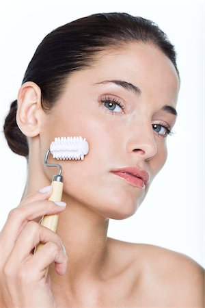 Young woman using facial massage roller Stock Photo - Premium Royalty-Free, Code: 6108-05869062