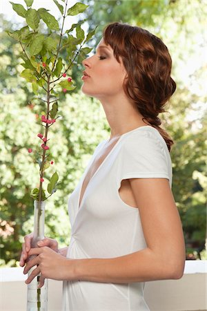 smelly - Young woman smelling plant Stock Photo - Premium Royalty-Free, Code: 6108-05869118