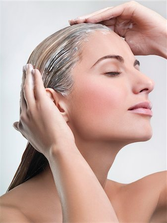 Young woman applying hair mask Stock Photo - Premium Royalty-Free, Code: 6108-05869225