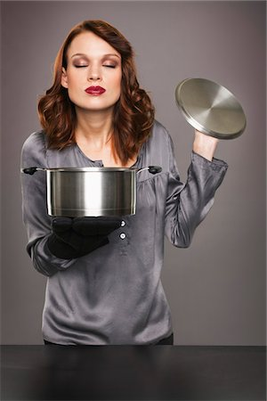 smelly - Young woman smelling aroma from stew pot Stock Photo - Premium Royalty-Free, Code: 6108-05869307