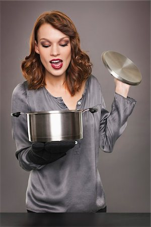 smelly - Young woman looking at content of stew pot Stock Photo - Premium Royalty-Free, Code: 6108-05869331