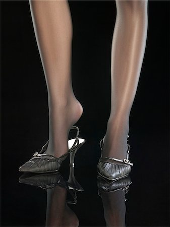 stocking feet - Woman putting on shoe, close-up Stock Photo - Premium Royalty-Free, Code: 6108-05869442