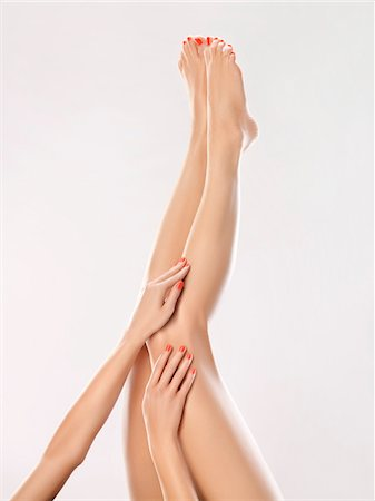 Woman touching her legs Stock Photo - Premium Royalty-Free, Code: 6108-05869422