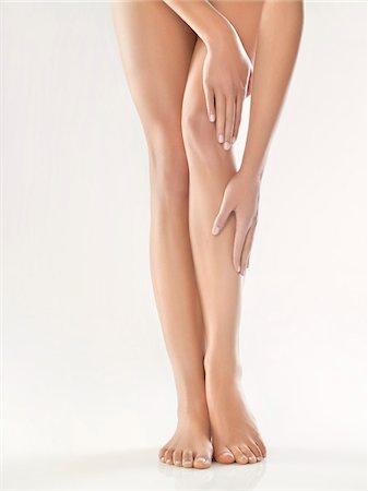 foot massage - Woman touching her legs Stock Photo - Premium Royalty-Free, Code: 6108-05869432