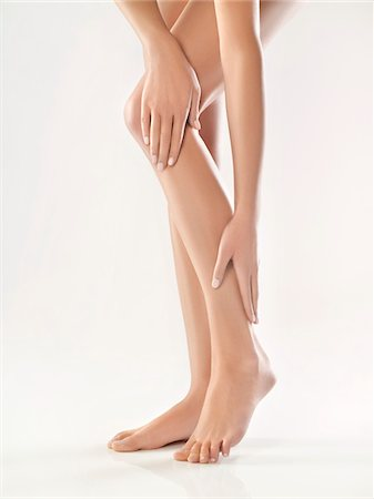 foot massage - Woman touching her legs Stock Photo - Premium Royalty-Free, Code: 6108-05869438