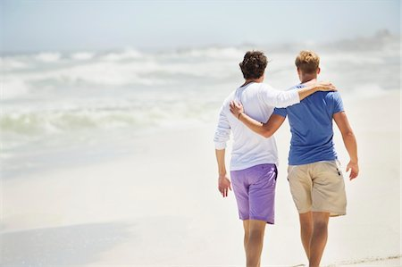 Rear view of two men walking with their arms around each other Stock Photo - Premium Royalty-Free, Code: 6108-05869668