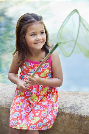 Little girl sitting by the swimming pool with net in hand Stock Photo - Premium Royalty-Free, Code: 6108-05869726