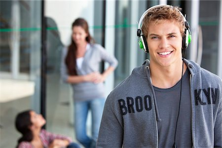 Portrait of a man listening to music with headphones in a campus Stock Photo - Premium Royalty-Free, Code: 6108-05869875