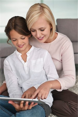 Woman assisting her daughter in using a digital tablet Stock Photo - Premium Royalty-Free, Code: 6108-05870065