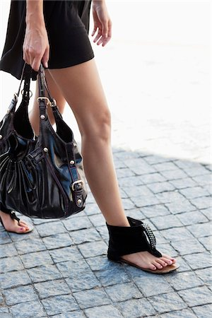 Low section view of a young woman wearing modern flat sandal and walking Stock Photo - Premium Royalty-Free, Code: 6108-05870007