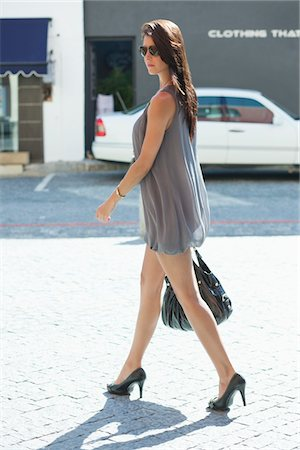Side profile of a young woman walking Stock Photo - Premium Royalty-Free, Code: 6108-05870035