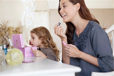 Young woman and little girl applying make-up at dressing table Stock Photo - Premium Royalty-Free, Code: 6108-05870185