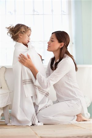 Woman wrapping her daughter in towel after the bath Stock Photo - Premium Royalty-Free, Code: 6108-05870191
