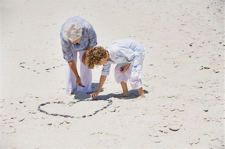 Senior woman and her grandson making a heart shape on the beach Stock Photo - Premium Royalty-Free, Code: 6108-05870131