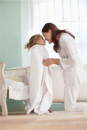 Woman rubbing noses with her daughter wrapped in towel after the bath Stock Photo - Premium Royalty-Free, Code: 6108-05870225