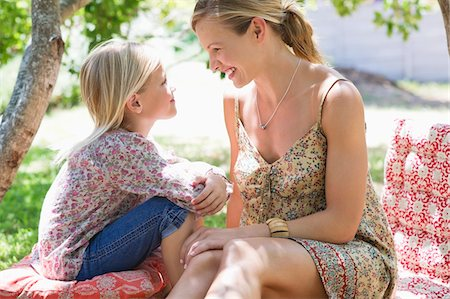 elementary age - Side profile of mother and a little girl looking to each other outdoors Stock Photo - Premium Royalty-Free, Code: 6108-05870384