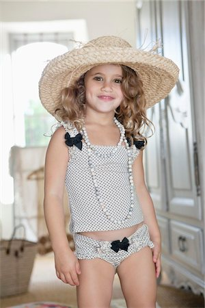 Portrait of a little girl dressed like her mother in oversized accessories Stock Photo - Premium Royalty-Free, Code: 6108-05870445