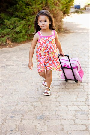 pulling - Little girl pulling a bag Stock Photo - Premium Royalty-Free, Code: 6108-05870446