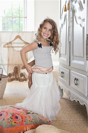 Cute little girl getting dressed like her mother in oversized clothes Stock Photo - Premium Royalty-Free, Code: 6108-05870467