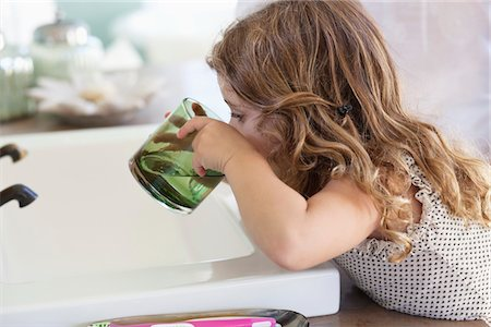 Cute little girl drinking water at bathroom sink Stock Photo - Premium Royalty-Free, Code: 6108-05870470