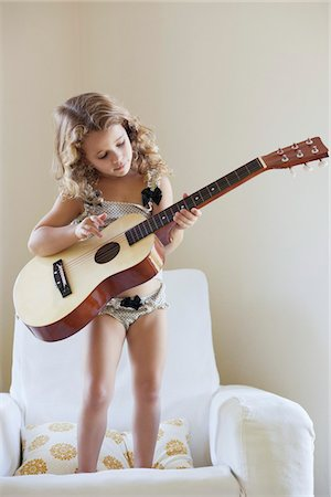 Cute little girl standing on a sofa and playing a guitar Stock Photo - Premium Royalty-Free, Code: 6108-05870472