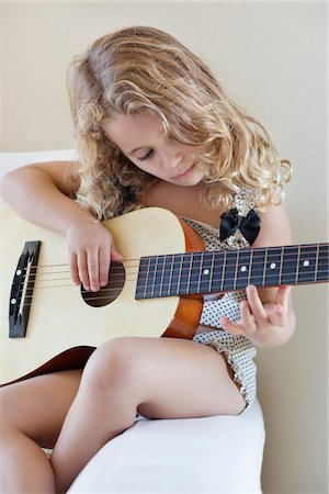 Cute little girl playing a guitar Stock Photo - Premium Royalty-Free, Code: 6108-05870481