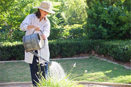 Senior woman in straw hat watering plants in a garden Stock Photo - Premium Royalty-Free, Code: 6108-05870490
