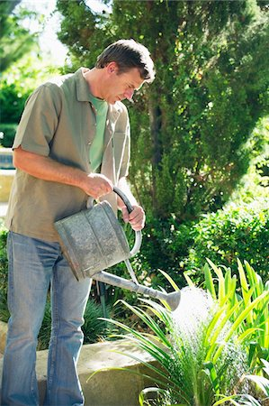 Mature man watering plants in a garden Stock Photo - Premium Royalty-Free, Code: 6108-05870495